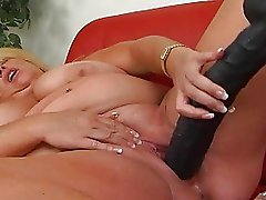 Huge blonde momma with massive bosom masturbates on sofa