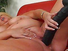 Huge blonde momma with massive bosom masturbates on sofa