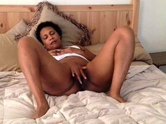 Lustful caramel mom lies on the bed and fingers her peach