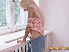 Blonde teen in jeans stripteases