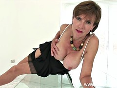 The mature with massive tits teasing on a glass table